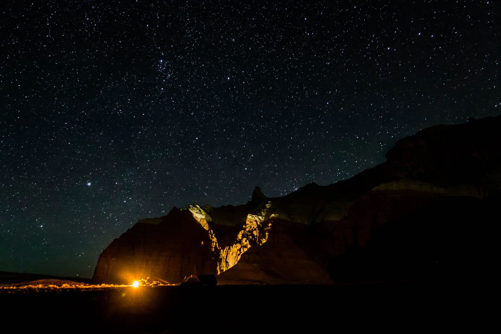 Night sky in Goblin Valley with camping fire lighting the mountain