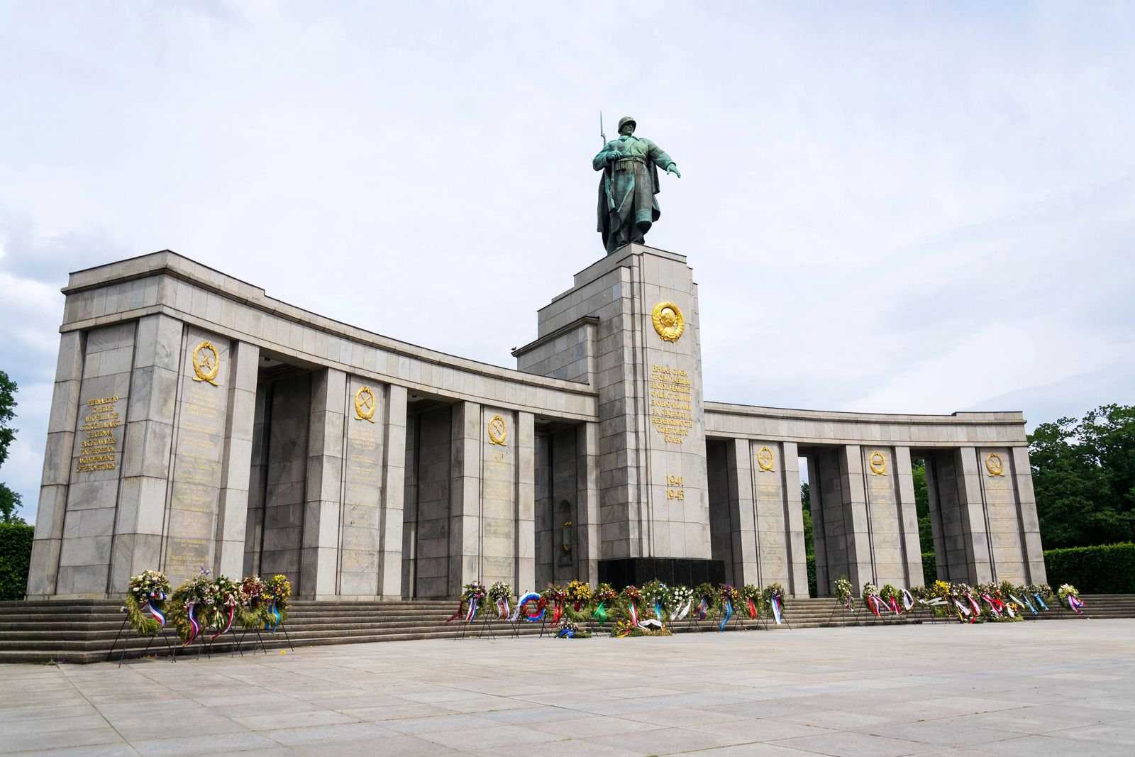 backpacking Eastern Europe 12 hours in berlin and what to see. Picture of grey soviet memorial with wreaths lain at the base