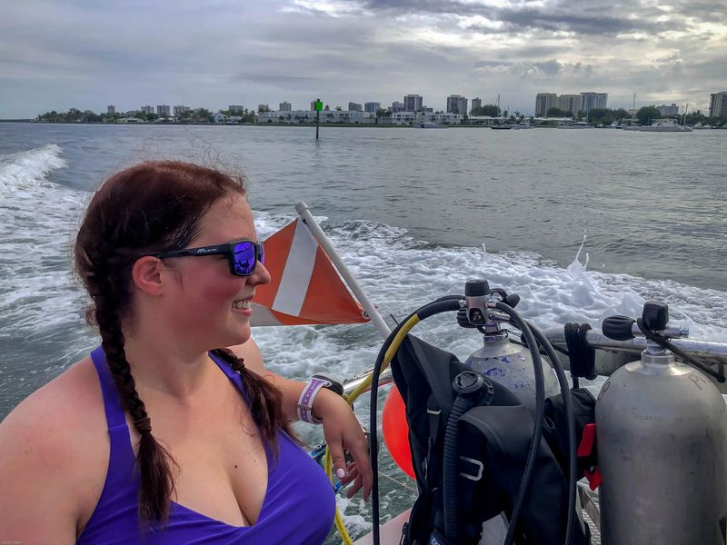 Woman sitting on a boat headed to Scuba dive off singer island in florida