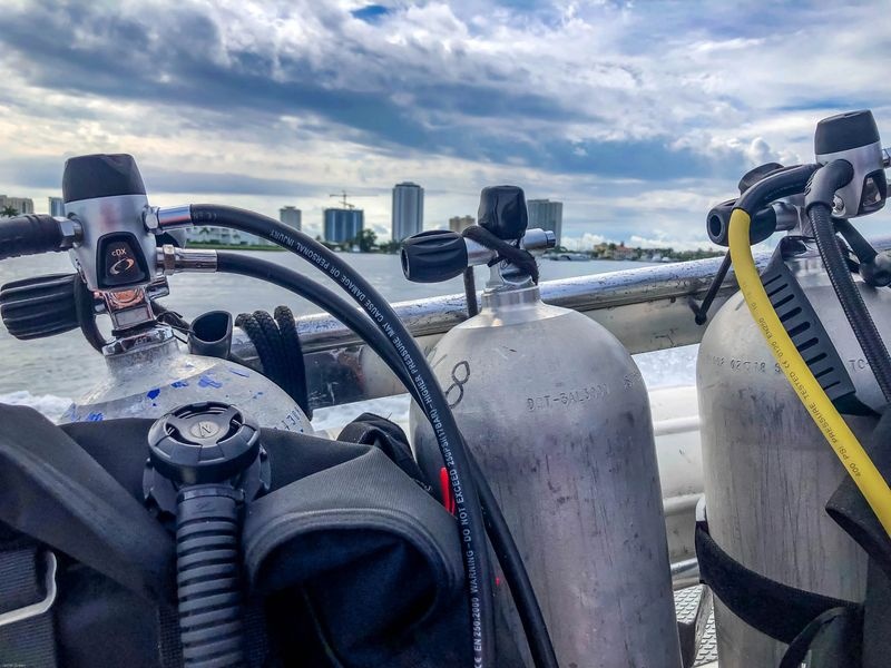 Diving Singer Island Florida - Scuba tanks on a boat rail with singer island hotels in the background